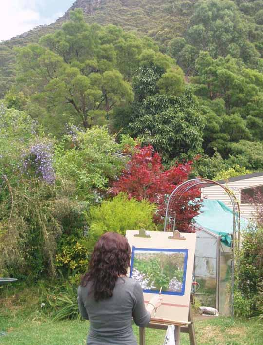 student painting outside studio, with view of illawarra escarpment
